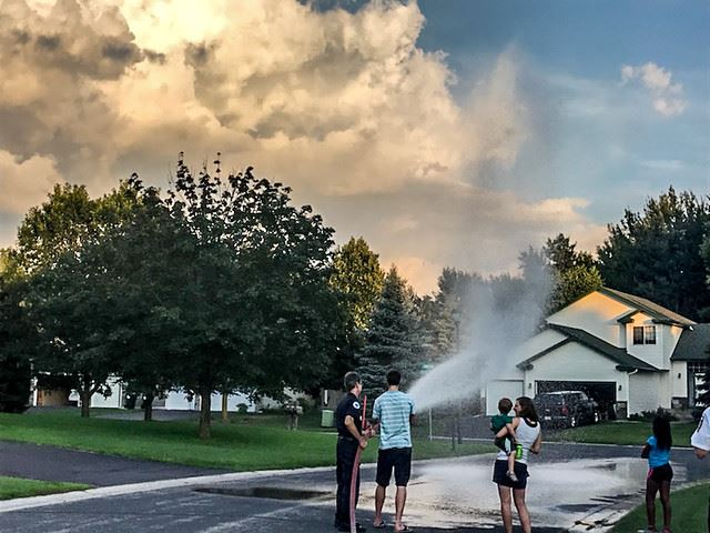 Firefighter with Neighbors Using Fire Hose