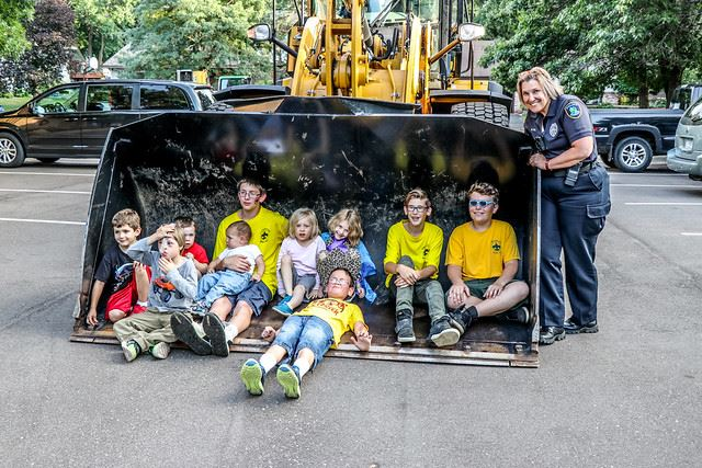 Officer Leaning on Front End Loader from Public Works with Children in the Sitting in the Shovel