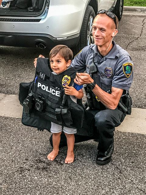 Officer Holding Bulletproof Vest Up on Child