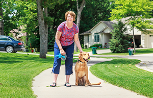 Woman Standing by Dog Sitting on Leash in Neighborhood - 300