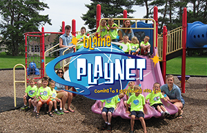 Blaine PlayNet - Coming to a Playground Near You - Photo of kids and leaders in the park on a slide.